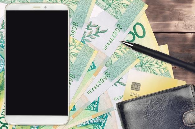 Contas de 50 rublos bielorrussos e smartphone com bolsa e cartão de crédito. conceito de pagamentos eletrônicos ou comércio eletrônico. compras online e negócios com uso de dispositivos portáteis Foto Premium