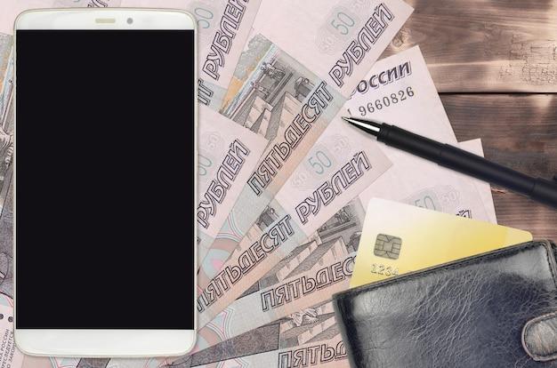 Contas de 50 rublos russos e smartphone com bolsa e cartão de crédito. conceito de pagamentos eletrônicos ou comércio eletrônico. compras online e negócios com uso de dispositivos portáteis Foto Premium