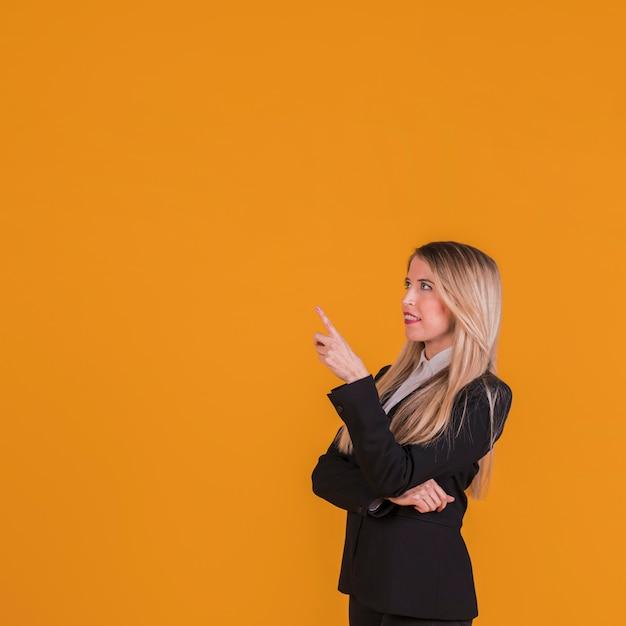 Contemplado jovem empresária apontando o dedo contra um fundo laranja Foto gratuita