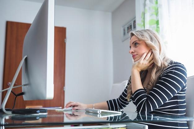 Contemplado jovem empresária sentado no escritório Foto gratuita