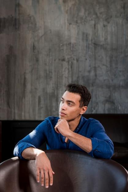 Contemplado jovem sentado atrás da cadeira contra parede cinza Foto gratuita