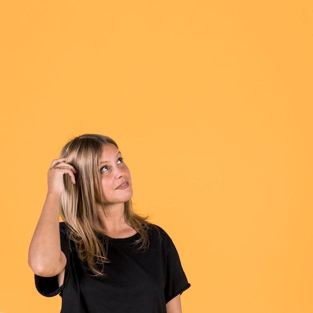 Contemplando a jovem mulher olhando para cima sobre o pano de fundo amarelo Foto gratuita