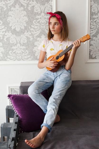 Contemplando a menina segurando ukulele desviando o olhar em casa Foto gratuita