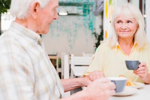 Conteúdo casal de idosos bebendo chá e segurando as mãos Foto gratuita