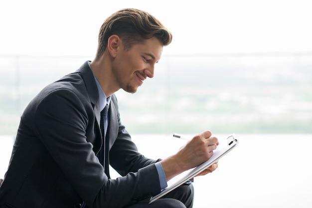 Conteúdo do homem de negócios que faz anotações meia-idade Foto gratuita