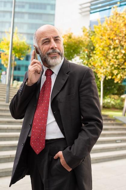 Conteúdo empresário falando pelo smartphone e procurando Foto gratuita