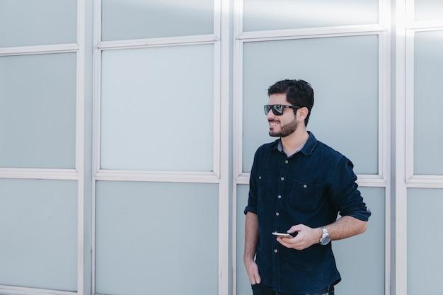 Conteúdo homem elegante com smarpthone Foto gratuita