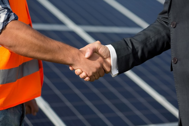 Contramestre e homem de negócios que agitam as mãos na estação da energia solar. Foto Premium