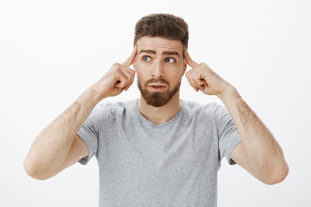 Controle-se e pense. retrato de um homem bonito preocupado e inseguro com barba e bigode tocando as têmporas com os dedos olhando para o canto superior esquerdo preocupado enquanto pensa Foto gratuita
