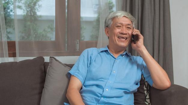 Conversa asiática do homem sênior no telefone em casa. o homem chinês mais velho asiático que usa o telefone celular que fala com neto da família caçoa ao encontrar-se no sofá no conceito da sala de visitas em casa. Foto gratuita