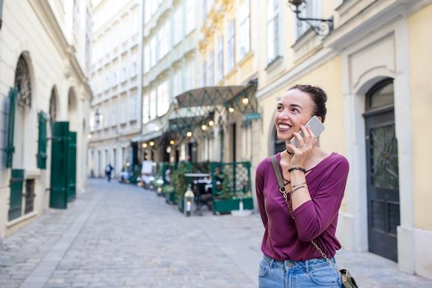 Conversa da mulher por seu smartphone na cidade. jovem atrativos turísticos ao ar livre na cidade italiana Foto Premium
