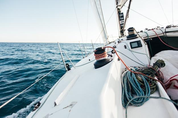 Convés de um veleiro profissional ou iate de corrida durante a competição em um dia ensolarado e ventoso de verão, movendo-se rapidamente através das ondas e da água, com a spinnaker levantada Foto gratuita