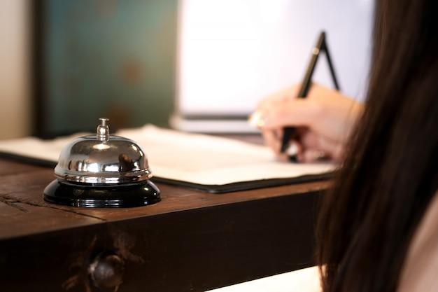Convidado da mulher na recepção do hotel que registra dentro Foto Premium