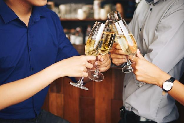 Convidados irreconhecíveis da festa torcendo com champanhe no bar Foto gratuita