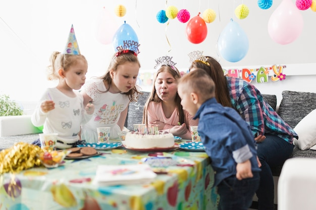 Convidados soprando velas no bolo Foto gratuita