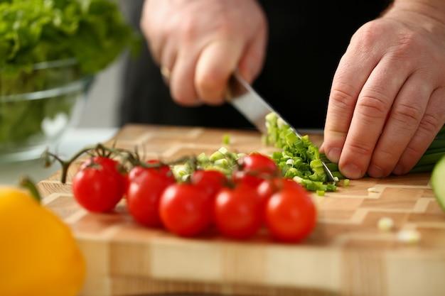 Cook segura a faca na mão e corta Foto Premium
