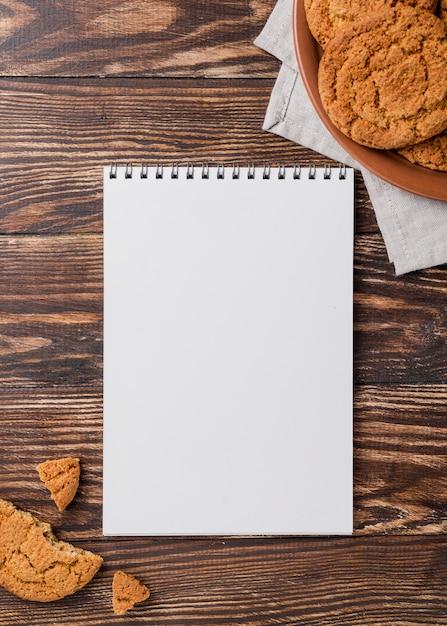 Cookies de vista superior e bloco de notas vazio de espaço de cópia Foto gratuita