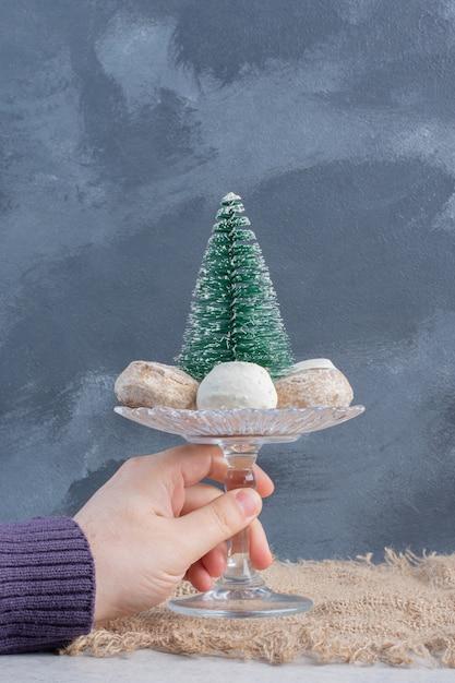 Cookies em torno de uma estatueta de árvore em um pequeno pedestal, segurada por uma mão sobre uma superfície de mármore Foto gratuita