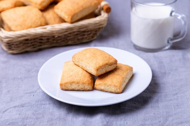 Cookies em um prato branco. uma cesta de biscoitos e um copo de leite. fechar-se. Foto Premium