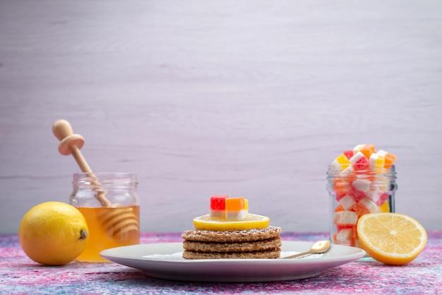 Cookies redondos de vista frontal junto com uma mesa de mel e limão Foto gratuita