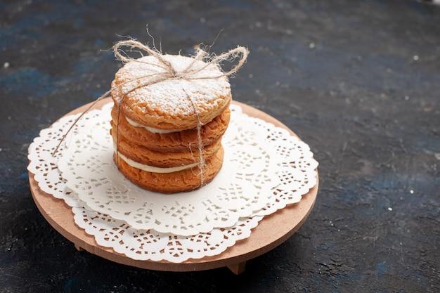 Cookies sanduíche de vista frontal com recheio de creme na superfície escura Foto gratuita