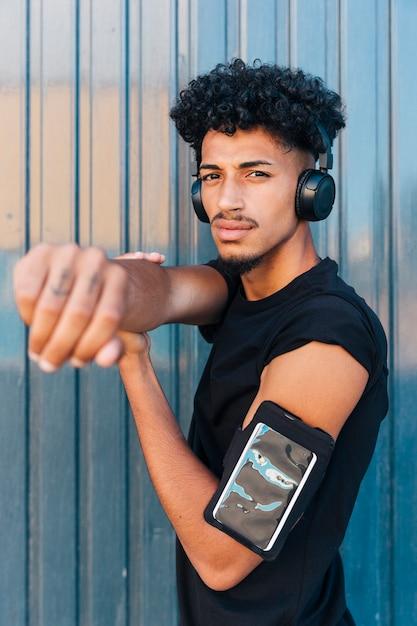 Cool étnica com braçadeira de telefone e fones de ouvido Foto gratuita