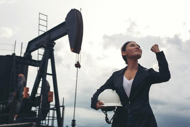 Coordenador fêmea que está com as bombas de óleo de trabalho com um céu branco. Foto gratuita
