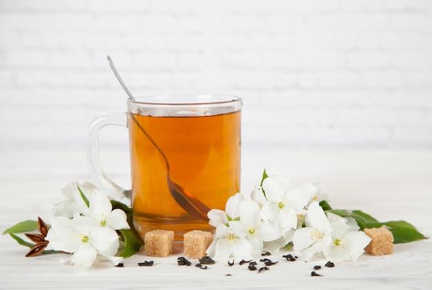 Copa com chá e flores de jasmim sobre um fundo branco Foto Premium