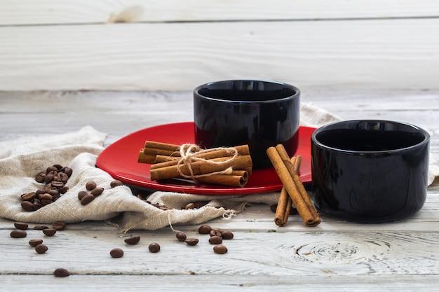 Copa preta, fundo de madeira, bebidas, manhã de natal, grãos de café, paus de canela Foto gratuita