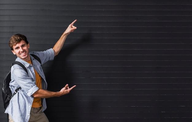 Cópia-espaço com homem apontando para o fundo Foto gratuita