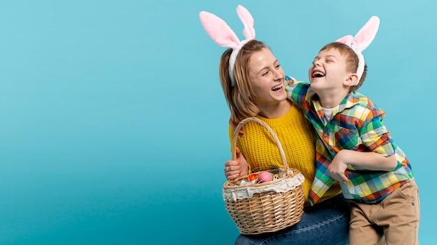 Cópia-espaço feliz mãe e filho com cesto de ovos pintados Foto gratuita