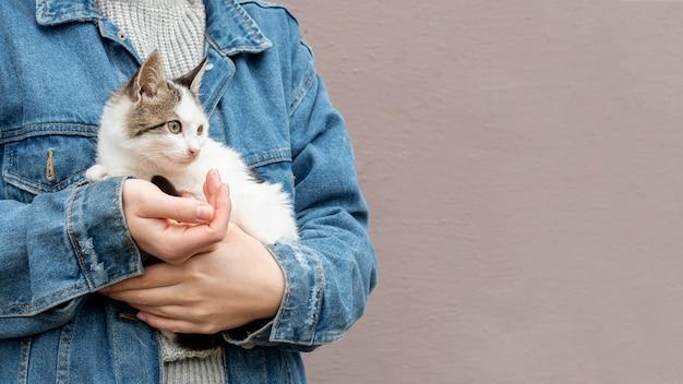 Cópia-espaço gato bonito sentado nos braços do proprietário Foto gratuita