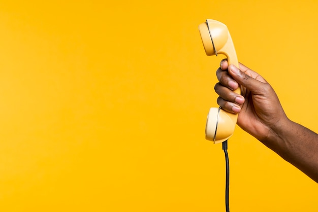 Cópia-espaço homem segurando o telefone antigo Foto gratuita