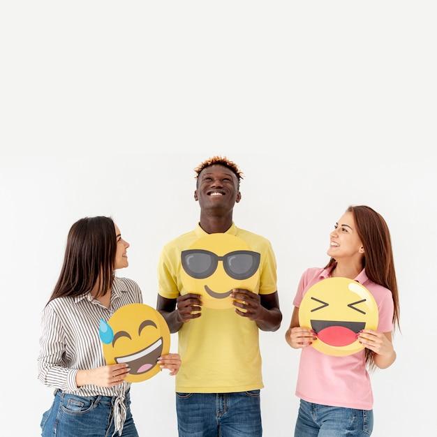 Cópia-espaço jovens amigos segurando emoji Foto gratuita