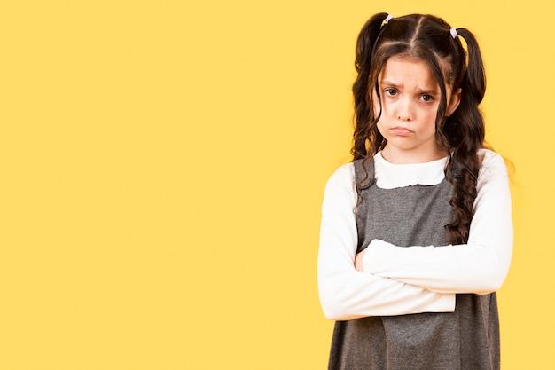 Cópia-espaço menina chateada em fundo amarelo Foto gratuita