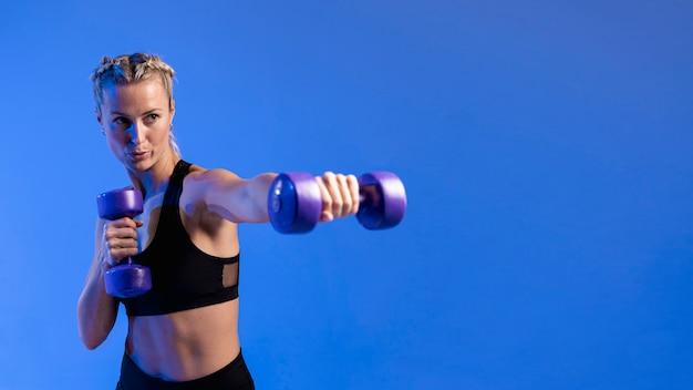 Cópia-espaço mulher treinando com pesos Foto gratuita