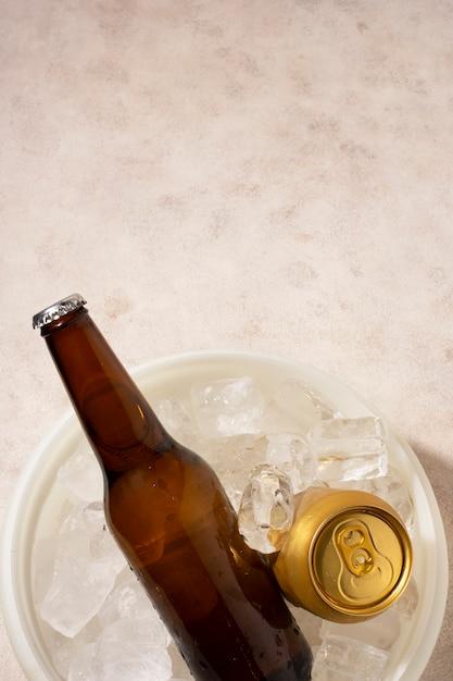 Copie o espaço de batalha de cerveja e pode no balde com cubos de gelo Foto gratuita