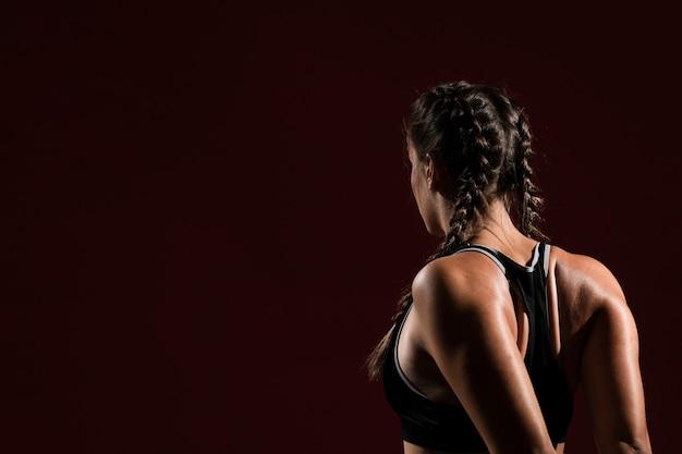 Copie o espaço e a mulher no fundo escuro por trás do tiro Foto gratuita