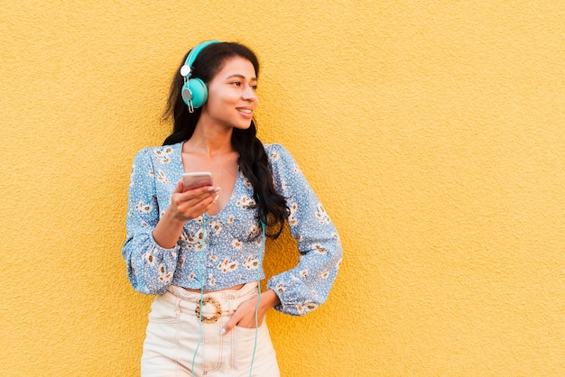 Copie o espaço fundo amarelo com mulher e fones de ouvido Foto gratuita