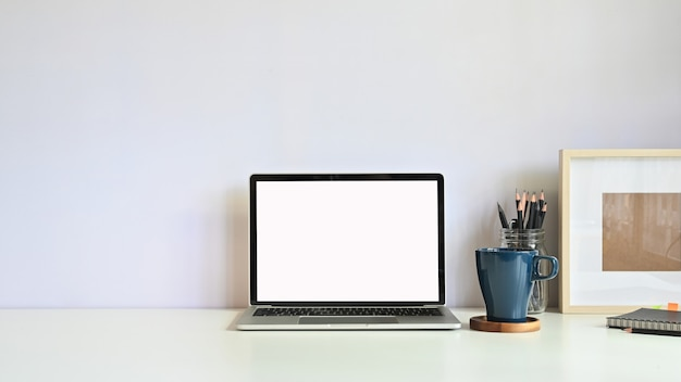 Copie o espaço maquete laptop, caneca de café, lápis com moldura na mesa do espaço de trabalho. Foto Premium