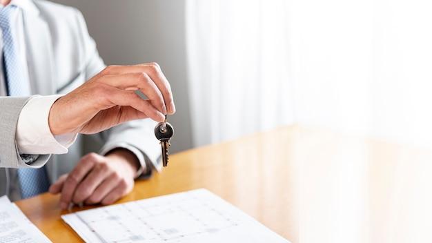 Copie o fundo do espaço com o homem segurando as chaves Foto gratuita