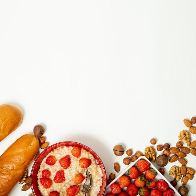 Copie o mingau de espaço com morangos e arranjo de nozes no fundo liso Foto gratuita