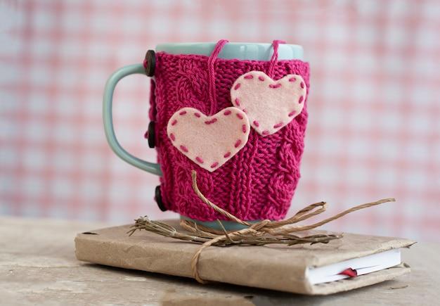 Copo azul em um suéter rosa em pé sobre um caderno velho Foto Premium