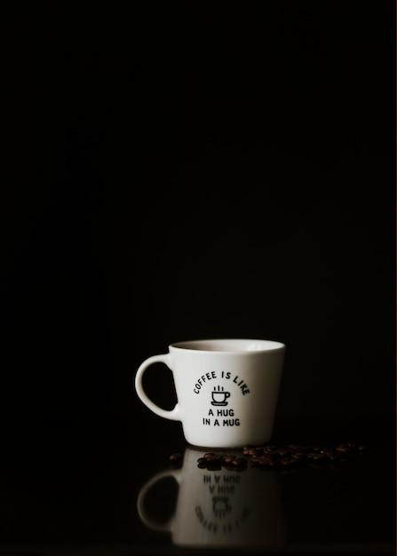 Copo branco cerâmico com grãos de café torrados em fundo preto Foto gratuita