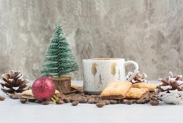 Copo branco cheio de café com grãos de café e pinhas. foto de alta qualidade Foto gratuita