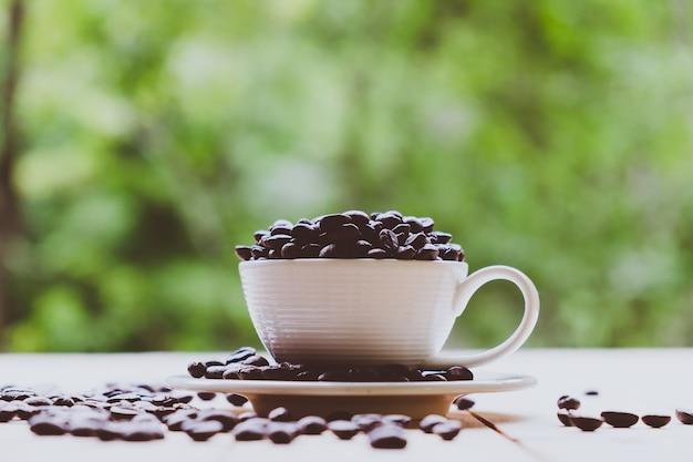 Copo branco cheio de grãos de café em feijões de café torrados e mesa de madeira no fundo da natureza Foto Premium