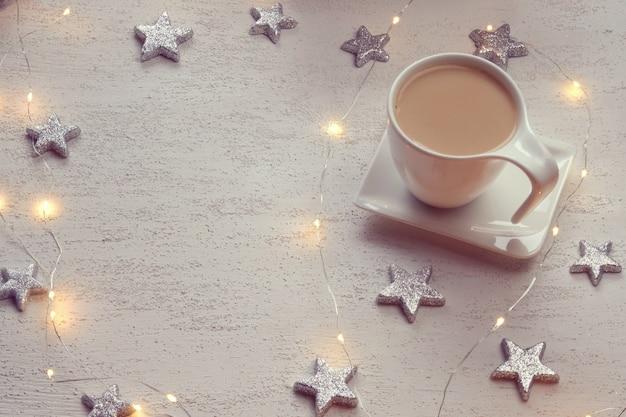 Copo branco com cacau, estrelas decorativas prateadas, guirlanda brilhante Foto Premium