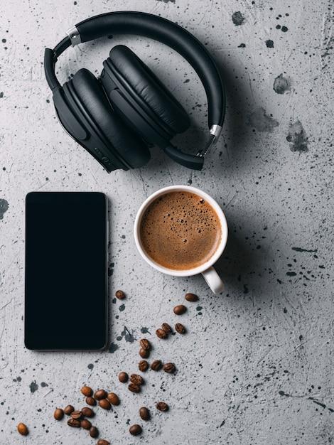 Copo branco com café perfumado para o café da manhã. telefone e fones de ouvido na mesa. final de semana Foto Premium