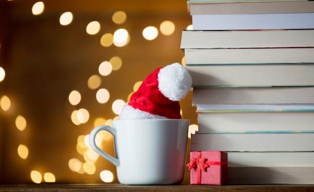 Copo branco com chapéu de natal e livros Foto Premium
