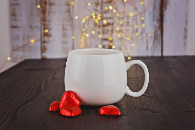 Copo branco com corações vermelhos dos doces de chocolate do valentim Foto Premium
